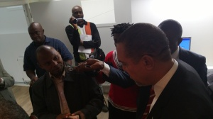 A passport officer at the embassy showing Amb Amobi how the machine works