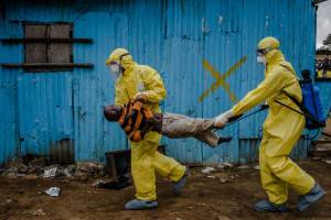 Medical staff carry James Dorbor, 8, suspected of having Ebola, into a treatment facility in Monrovia, Liberia, Sept. 5, 2014.  Ebola ó the reality and the hysteria over it ó  is having a serious economic impact on Guinea, Liberia and Sierra Leone, three nations already at the bottom of global economic and social indicators. (Daniel Berehulak/The New York Times)